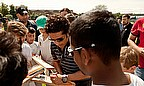 Sachin headed to a local club in London on the day the coin was launched - here he signs autographs