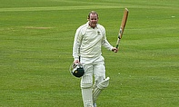 Dave Carlyle raises his bat after scoring his century