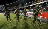 Sri Lanka's Special Task Force soldiers walk towards Pakistan's dressing room after the team walked off field after a clash between supporters in the