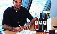 James Anderson, with bottles of his Numbers Collection, signs his Lord's Taverners membership form