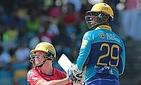 Colin Munro (left) attempts a reverse sweep against Barbados Tridents.