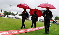 Officials examine the pitch as rain delays play in Derby