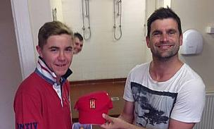 15-year-old Dominic Scott is handed his cap by Ian Hunter ahead of his debut
