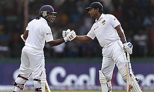 Mahela Jayawardene (left) and Kumar Sangakkara shake hands during their half-century partnership