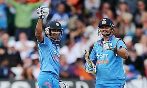 Ambati Rayudu (left) celebrates his half-century against England as Suresh Raina looks on