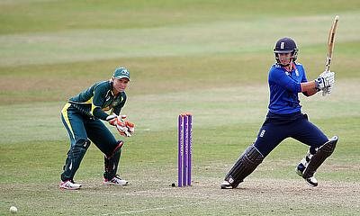 Georgia Elwiss hits a shot as Alyssa Healy looks on