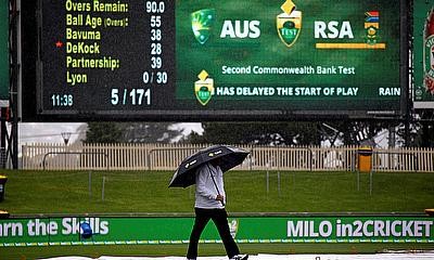 Umpire Mick Martell walks on a covered wet outfield in Hobart on day two