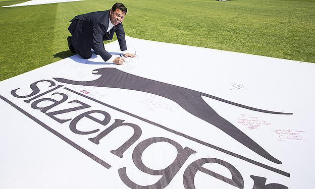 Warren Hegg signs the giant flag commissioned by Slazenger to commemorate James Anderson's record-breaking feat