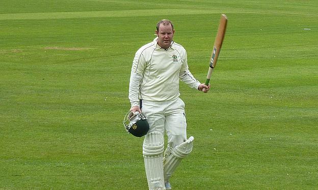 Dave Carlyle raises his bat after scoring his century