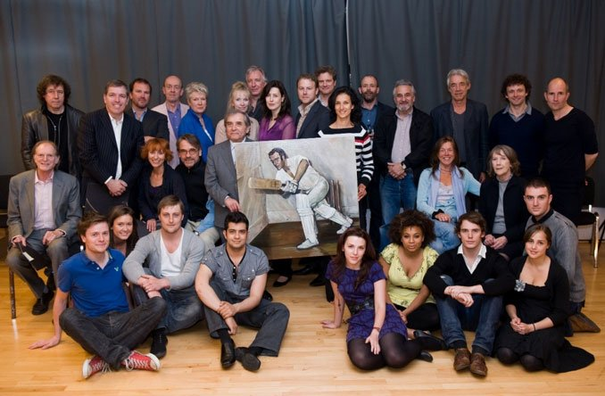 Actors pose alongside the picture
