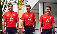 Dawid Malan (left), Joe Root and captain Eoin Morgan model England's red shirt they will wear against Scotland