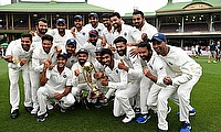 The Indian team poses for a photograph with the Border-Gavaskar Trophy as they celebrate a 2-1 series victory over Australia