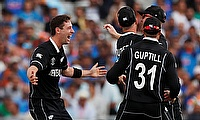 New Zealand's Matt Henry and James Neesham celebrate taking the wicket of India's Dinesh Karthik