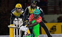 Sherfane Rutherford (R) of Guyana Amazon Warriors hits 4 as Glenn Phillips (L) and Chris Gayle (C) of Jamaica Tallawahs