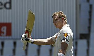 Steve Smith raises his bat