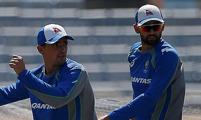 Australia's Steve O'Keefe (L) bowls as Nathan Lyon watches