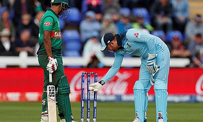 England's Jonny Bairstow inspects the stumps after the ball hit them and the bails did not fall as Bangladesh's Mohammad Saifuddin looks on