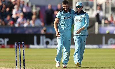 England's Mark Wood celebrates with Eoin Morgan after taking the wicket of New Zealand's Matt Henry