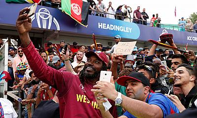Chris Gayle poses for a photo with fans as he celebrates after the match