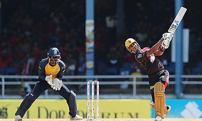 Lendl Simmons of Trinbago Knight Riders hits six as Andre Fletcher of St Lucia Zouks looks on