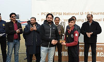 Former Test Player Saeed Ajmal giving away PCB U13 Catch em Young National One Day Tournament winner's trophy to Ahmed Hussain captain Khyber Pakhtun