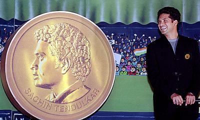 ndian batsman Sachin Tendulkar poses next to a giant replica of the 24-carat gold medallion presented to him in Bombay
