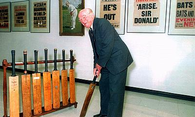Sir Donald Bradman holds one of his old cricket bats at the opening of the Bradman Collection