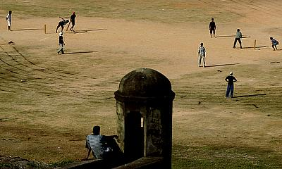 A man watches a cricket game as he sits on a wall of the World Heritage-listed Dutch Fort in Galle, Sri Lanka