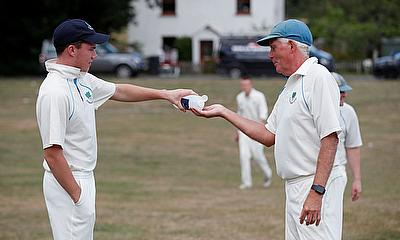 Members of the Tilford Cricket Club use hand sanitiser