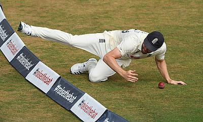 England's Chris Woakes stops a ball from hitting the boundary