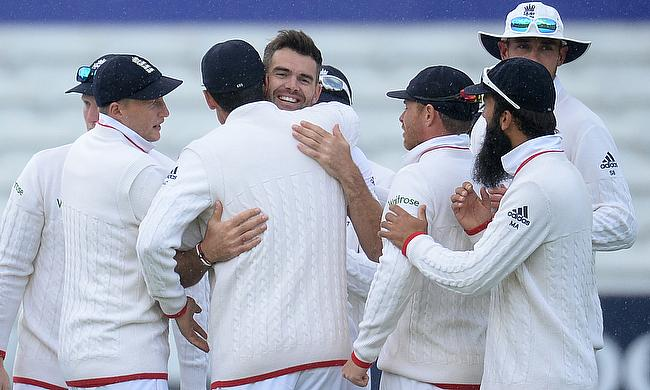 James Anderson being congratulated by his England teammates after achieving the milestone of 400 wickets in Test cricket.