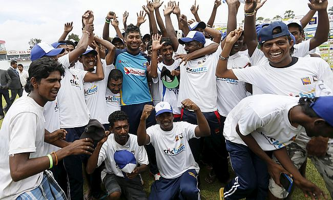 Kumar Sangakkara poses for pictures with Sri Lankan groundstaff in Colombo