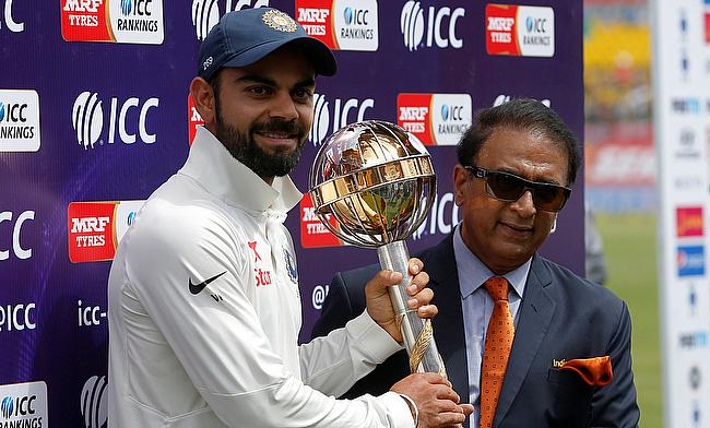 India's Virat Kohli receives the ICC Test Mace from former Indian cricket player Sunil Gavaskar (R) after India won the test series against Australia