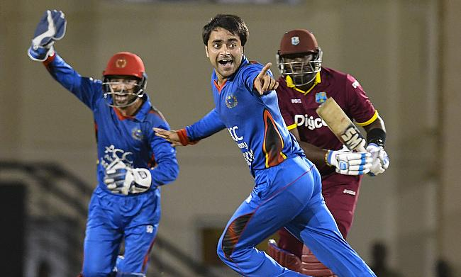 Rashid Khan (centre) celebrating the wicket of Ashley Nurse (right)