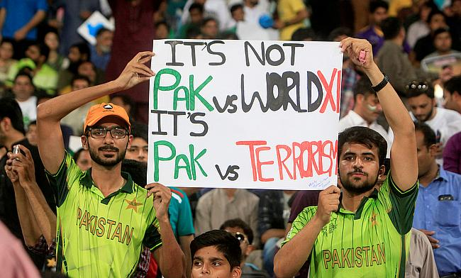 Spectators hold a sign during the final match of World XI cricket series in Lahore, Pakistan