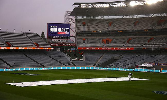 Umpire Wayne Knights stands near the covered pitch shortly before announcing play has been abandoned due to rain