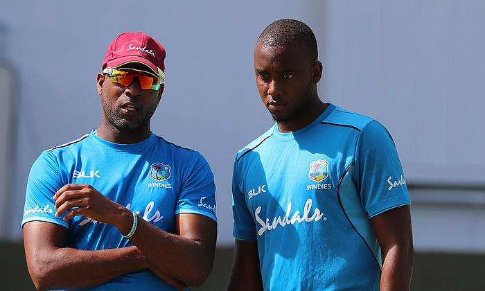 Coach Corey Collymore speaks to fast bowler Miguel Cummins