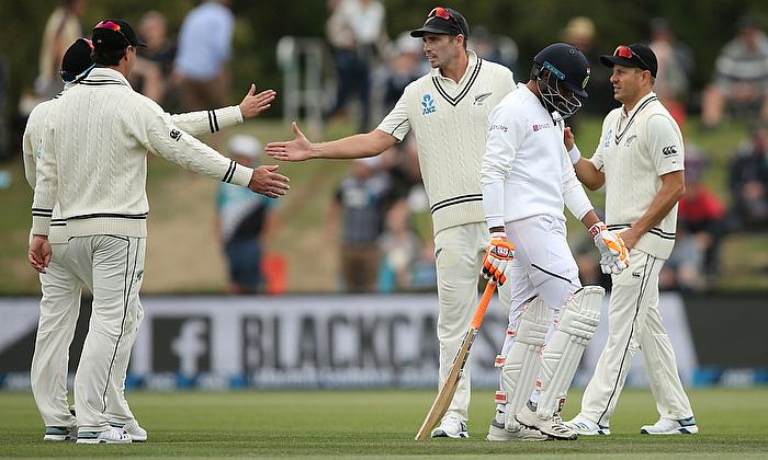 India's Ravindra Jadeja walks off dejected while New Zealand players celebrat