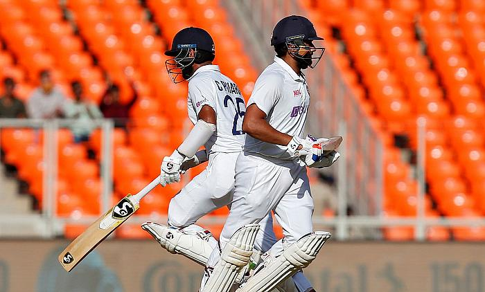 India's Cheteshwar Pujara and Rohit Sharma run between the wickets.