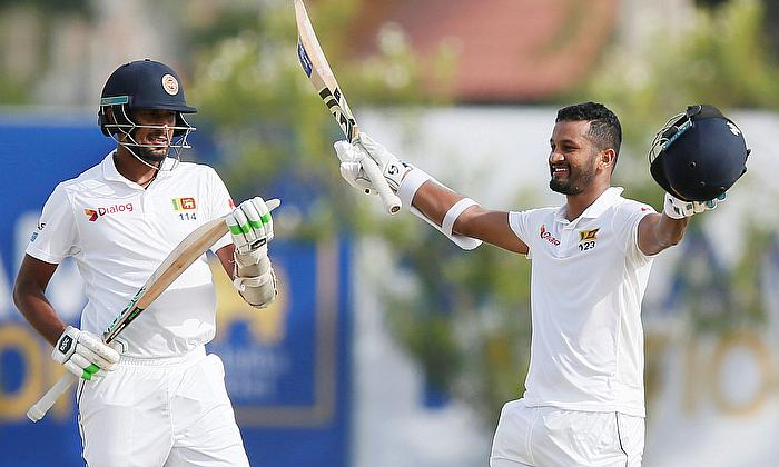 Sri Lanka's Dimuth Karunaratne (R) celebrates his century next to captain Suranga Lakmal