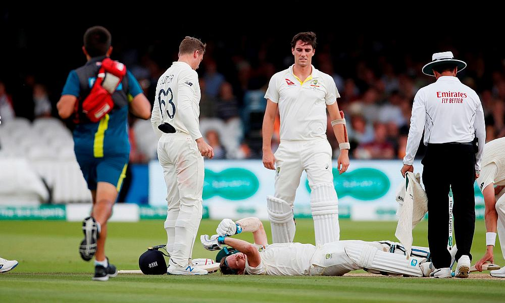 Australia's Steve Smith lays on the floor after being hit by a ball from England's Jofra Archer as England's Jos Buttler and Australia's Pat Cummins l