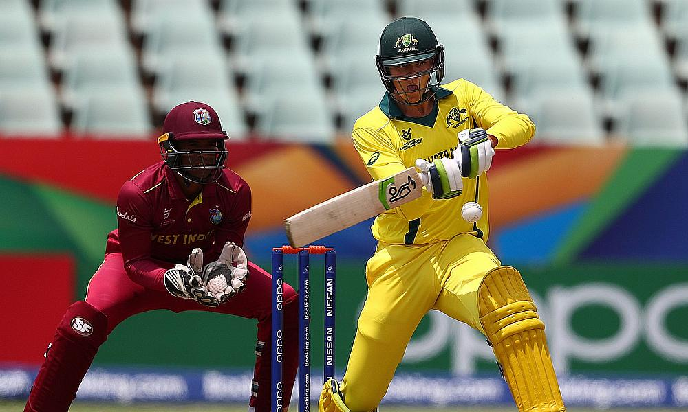 Liam Scott of Australia hits the ball towards the boundary, as Leonardo Julien of West Indies looks on during the ICC U19 Cricket World Cup