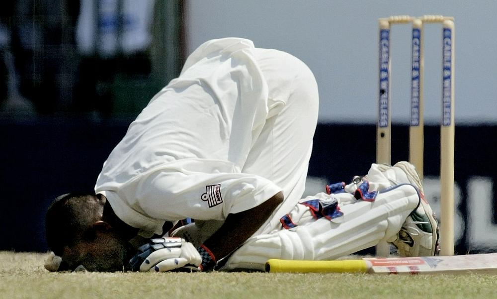 Shivnarine Chanderpaul kneels down to kiss the ground after scoring a century against Australia in first test in Georgetown, Guyana April 10, 2003