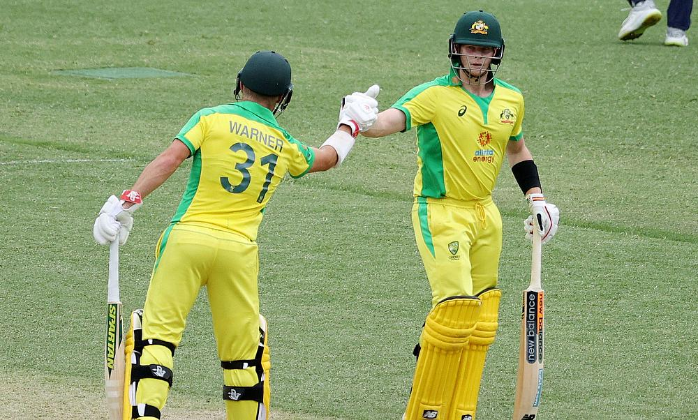 David Warner bumps fists with Steven Smith